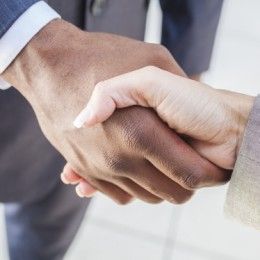 African American businessman or man shaking hands with a businesswoman or woman caucasian female colleague making a business deal