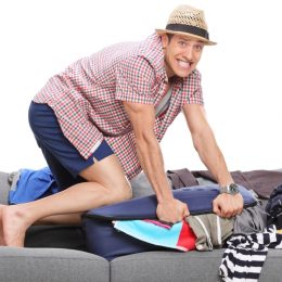 Young man packing a lot of clothes into one suitcase and looking at the camera isolated on white